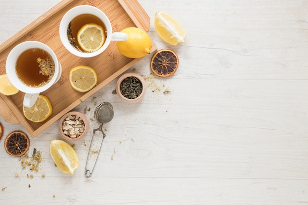 Lemon tea with lemons in tray and herbs on white wooden table