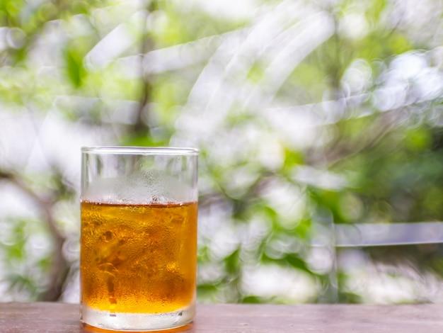 Lemon tea with nature green blur bokeh background