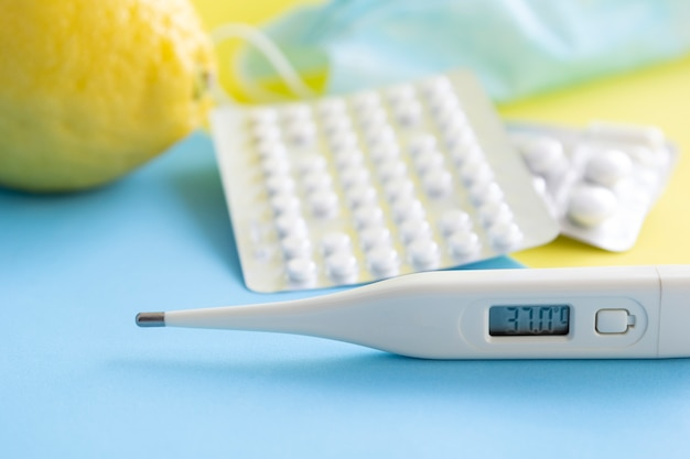 Lemon, thermometer, medical mask and medical pills, tablets from glass bottle on light background.