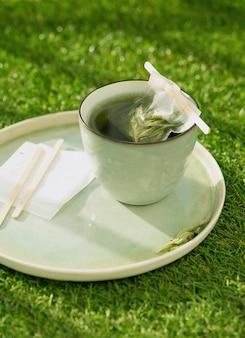 Чай с лимонной вербеной в кружке с чайным пакетиком ручной работы над травяным столом на балконе. концепция уюта. выборочный фокус. закройте вверх. естественный свет.