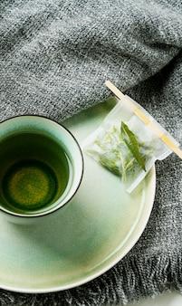 Лимонный чай с вербеной в кружке с заваренным вручную чайным пакетиком на сером одеяле. концепция уюта. вид сверху. flat lay
