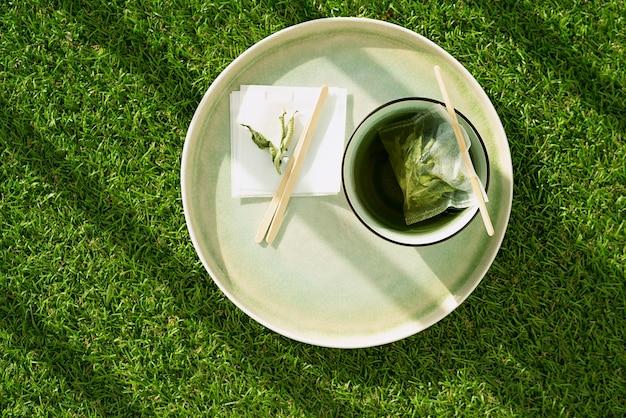 Лимонный чай с вербеной в кружке с чайным пакетиком ручной работы над зеленой травой. концепция уюта. закройте вверх. естественный свет.
