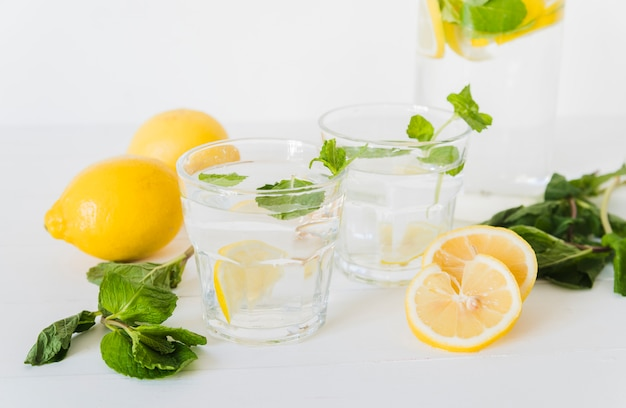 Lemon water in glasses and ingredients