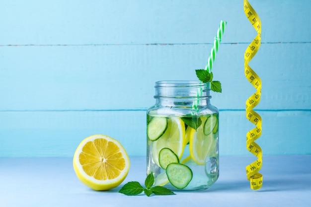 Lemon water, juicy lemon, mint and measuring tape