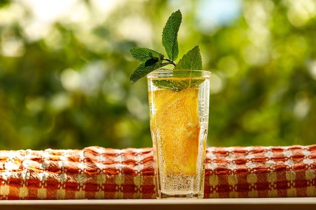 유리에 민트와 레몬 물. 여름 정원 배경입니다.