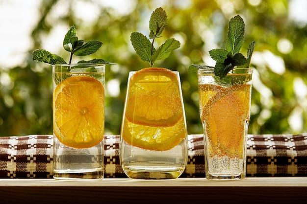 3つのグラスにミントを入れたレモン水。サマーガーデン。