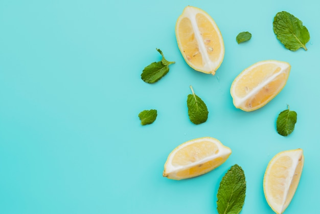 Lemon wedges and mint leaves on background