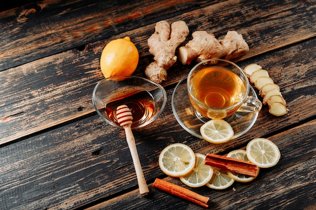 Lemon with ginger, honey, dry cinnamon, tea high angle view on a dark wooden background