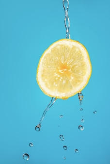 Лимон с собственным соком на синем фоне