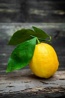 Lemon with leaves on dark wooden background, side view.