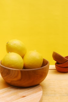 Lemon in wooden bowl with yellow background