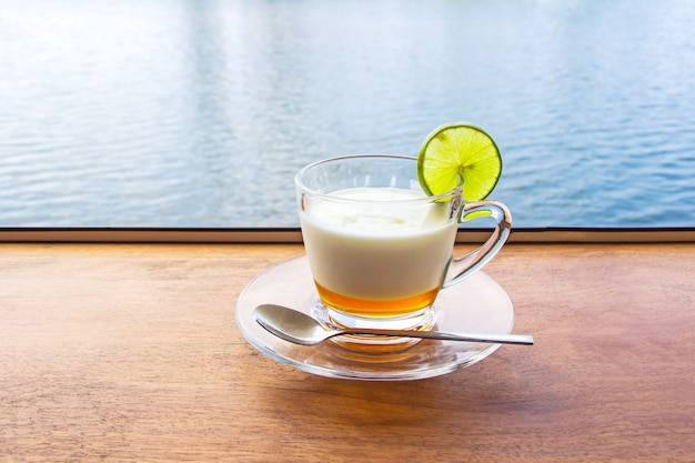 Lemon yogurt fresh milk in a clear glass placed on a brown wooden table with sea water surface.