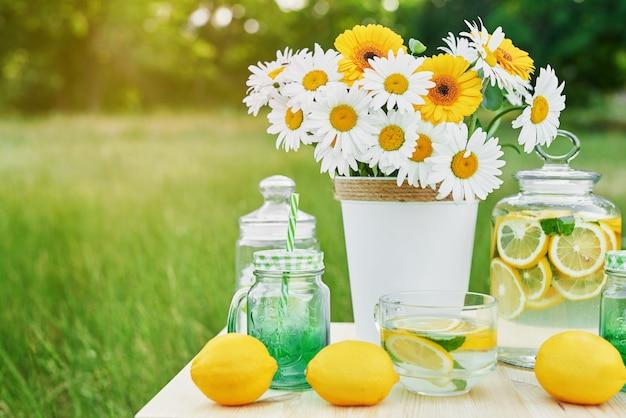 テーブルの上のレモネードとデイジーの花。レモンとレモネードのメイソンジャーガラス。屋外のピクニック。