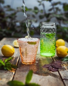 レモネードとガラスと木製と庭のテーブルの上の瓶の成分。側面図。