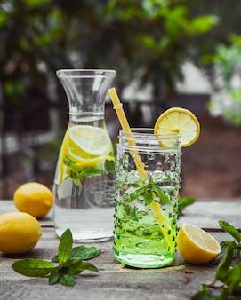 レモネードとガラスの水差しと木製と庭のテーブルの上の瓶の成分。側面図。