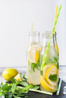 Lemonade in bottles with ice and mint