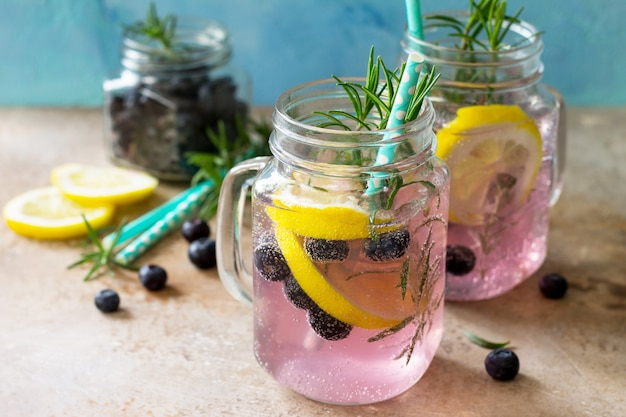 Lemonade or cocktail with blueberries lemon and rosemary cold refreshing drink with ice