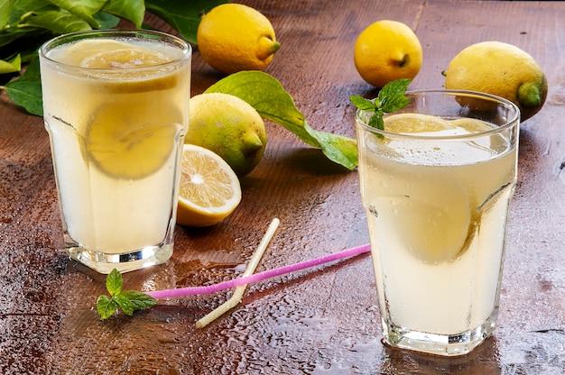 Лимонный напиток и лимоны с мятой на столе вудден
