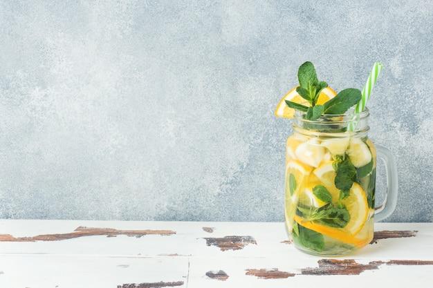 Lemonade drink of soda water, lemon and mint leaves in jar on light background.