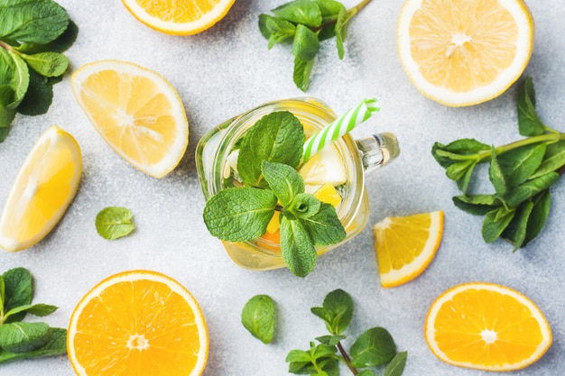 Lemonade drink of soda water, lemon and mint leaves in jar on light background.