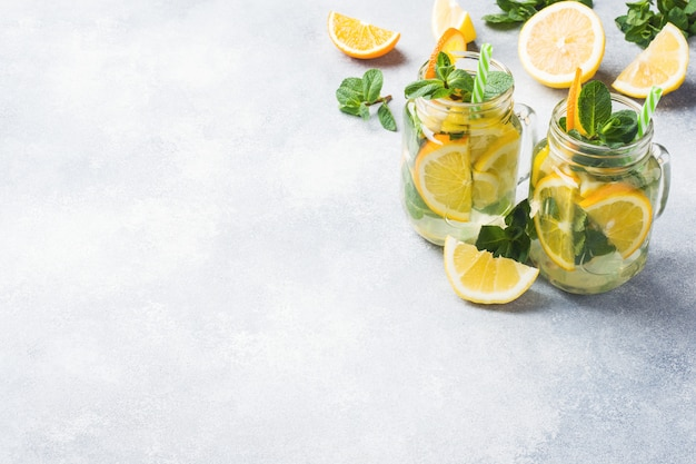 Lemonade drink of soda water, lemon and mint leaves in jar on light background