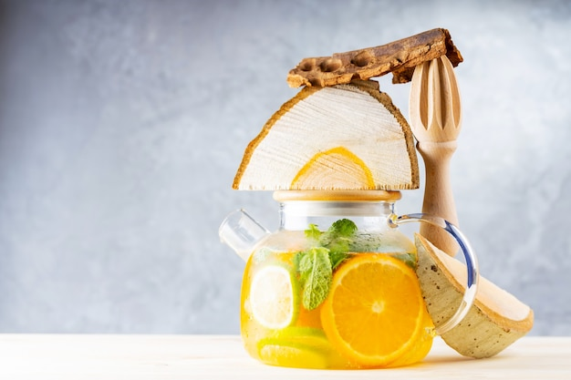 Lemonade drink of water, lemon, orange and mint leaves in a transparent teapot. lime mint iced tea and pieces of wood. creative composition