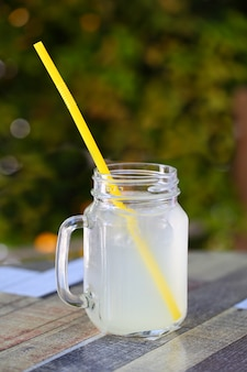 Lemonade fresh in a jar with a handle and a straw on the table.