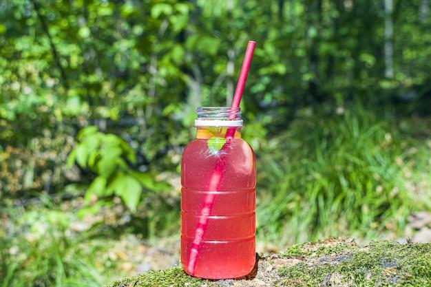 イチゴ、ラズベリー、グレープフルーツ、赤スグリのレモネード。モスと木材にピンクのカクテルを飲む