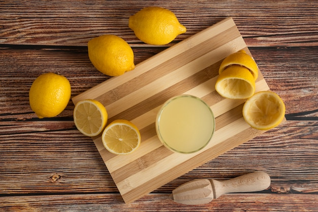 Lemonade in a glass cup on the wooden board, top view