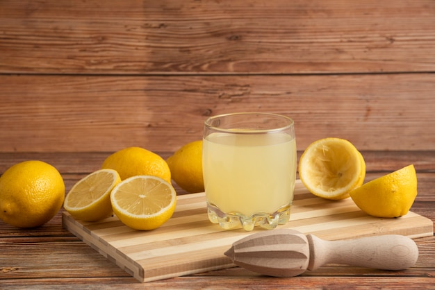 Lemonade in a glass cup on the wooden board