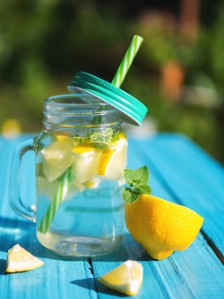 Lemonade in a glass jar with slices of lemon and mint on a wooden table