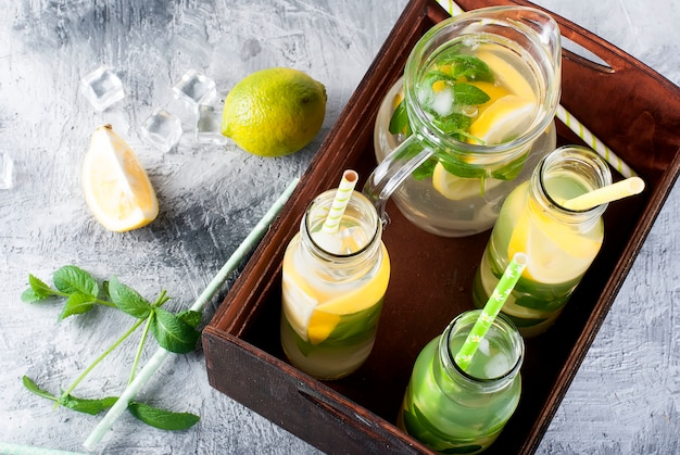 Lemonade in glass jug and bottles with ice and mint