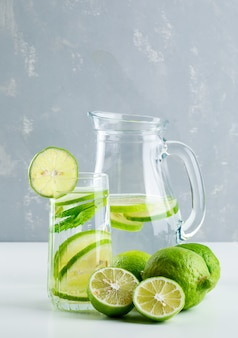 Lemonade in glass and jug with lemon, basil side view on white and plaster