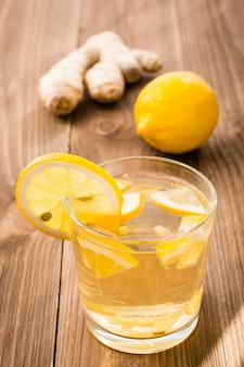 Lemonade in a glass, lemon and ginger on a wooden table