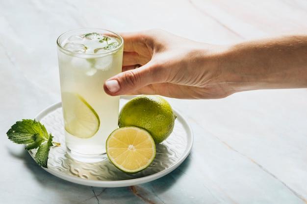 Lemonade glass and limes on bamble background