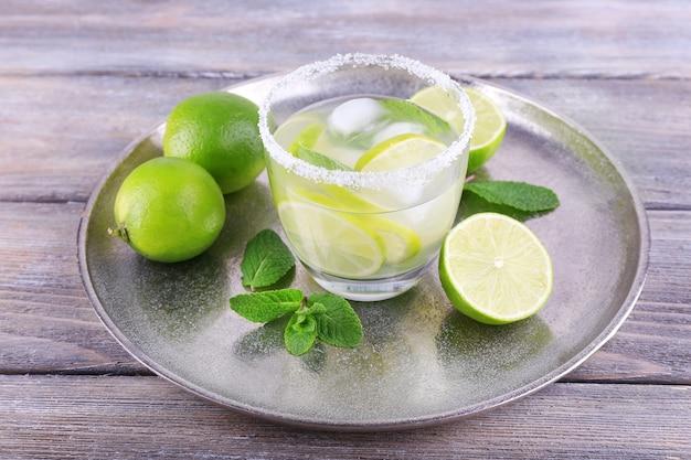Lemonade in glass on tray on wooden