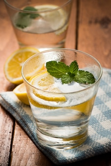 Lemonade on glass with ice on wooden