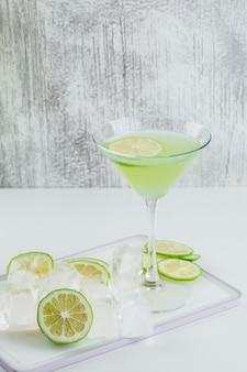 Limonata in un bicchiere con limone, tagliere, cubetti di ghiaccio vista laterale su bianco e sgangherata