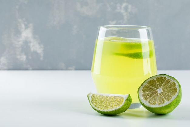 Lemonade in a glass with lemon side view on white and plaster