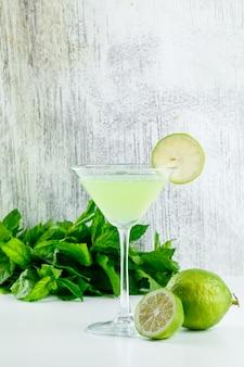Limonata in un bicchiere con limoni, foglie di basilico vista laterale su bianco e sgangherata