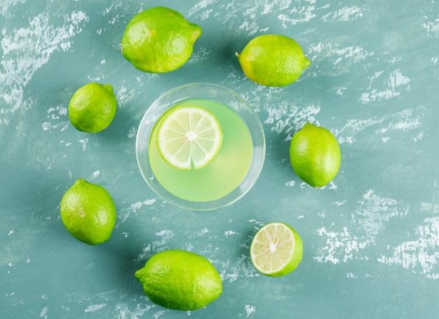 La limonata in un bicchiere con i limoni piatti giaceva su un cerotto