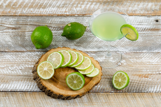Lemonade in a glass with lemons flat lay on wooden and cutting board
