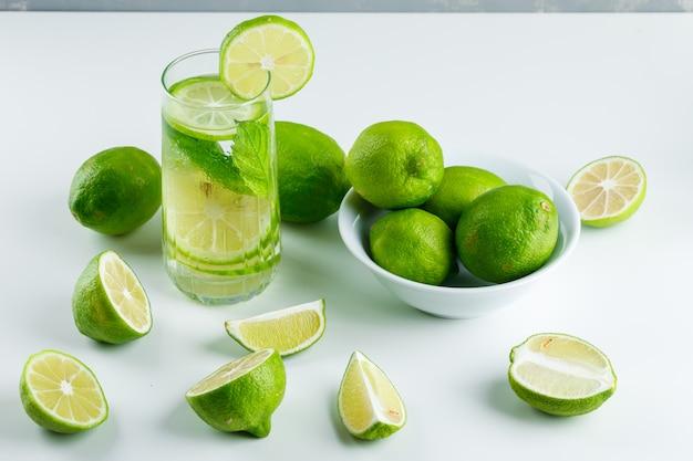 Limonata in un bicchiere con limoni, erbe veduta dall'alto su bianco e grigio