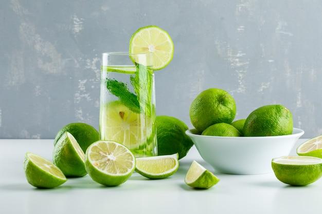 Limonata in un bicchiere con limoni, erbe vista laterale su bianco e gesso