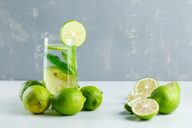 Lemonade in a glass with lemons, herbs side view on white and plaster