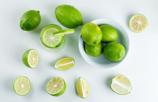 Limonata in un bicchiere con limoni, piatto di paglia disteso su un bianco