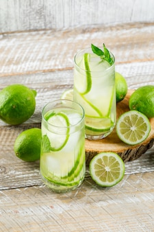 Lemonade in glasses with lemon, basil, cutting board high angle view on wooden and grungy