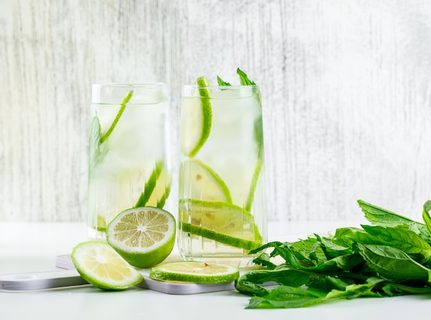 Lemonade in glasses with lemon, basil, cutting board side view on white and grungy