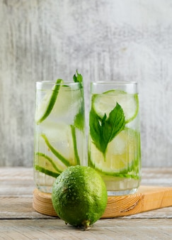 Lemonade in glasses with lemon, basil, cutting board side view on wooden and grungy