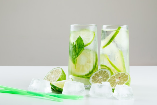 Lemonade in glasses with lemons, straws, basil, ice cubes side view on white and grey